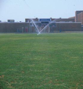 Sprinklers watering athletic field